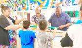 Gov. Lemanu Peleti Palepoi Sialega Mauga serving a line of children lunch