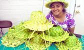 Rejoyce Saega displays her coconut leaf hats