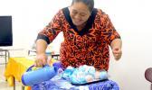 "Osana Esekia prepares to demonstrate her original product the ""bath bomb"""