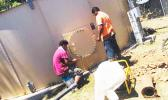 Two ASPA employees working on water tank in Aunu'u.