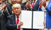 In this April 28, 2017, file photo, President Donald Trump holds up a signed Executive Order in the Roosevelt Room of the White House in Washington directing the Interior Department to begin review of restrictive drilling policies for the outer-continental shelf. The AP reported on May 26, 2017, that a story shared by the St. George Gazette website claiming Trump signed an executive order allowing the hunting of bald eagles is a hoax. (AP Photo/Pablo Martinez)