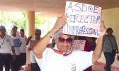 Man holds sign saying ASDOE director is unprofessional