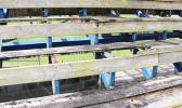 The wooden seating area at the baseball field is in such a rotted state, thanks in part to vandalism that has also left the seats with burn marks, and broken/splintered wood pieces. [photo: THA]