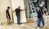 James Fujita, left, and Reid Fujita take down plywood boards