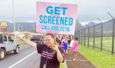 """Woman with """"get tested"""" sign for Breast Cancer Awarenss Month"""