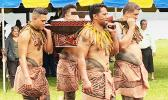 4 young men with traditional tattoos carry the 2020 American Samoa quarter in a tapa decorated box