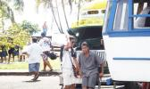 Street vendors in Apia around a bus.