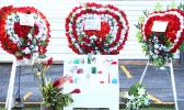 Flowers with photographs in place at the site where three Manu'a Store employees died