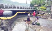 """Aua Village was the first to complete the challenge """"installation of marine debris encatchment net"""" on island, which was set up by American Samoa Power Authority and the village council. The net was set up at the stream on the main road of Aua. Aua 1st Ward of LDS faith adopted the stream and was very happy to have the net to help keep their coast clean and healthy. [photo: Ese Malala]"""