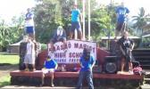 Fa'asao Marist High School sign with students standing near