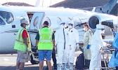 Ground crew and medical personnel on the tarmac at the Pago Pago International Airport