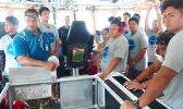USCG official Frank Thomsen with a group of local teens who toured the USCG Cutter Joseph Gerczak