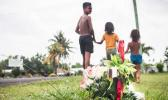 Village children walk past a cross planted at Faleula
