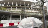 A woman walks past the New National Stadium, a venue for the opening and closing ceremonies at the Tokyo 2020 Olympics