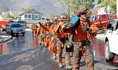 Firefighters march into an L.A. neighborhood threatened by wildfire.
