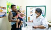 Nurse Fa'atafa Tavita (R) speaking with a father holding his child at the Apia Town Clinic