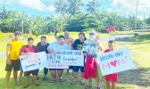 Families with signs welcoming their loved ones home