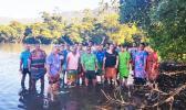 Village leaders at low tide among mangroves