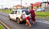 American Samoa Lieutenant Governor Lemanu pushing stalled car out of the way of traffic