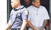 Manu Lefatia in handcuffs escorted by two police officers