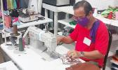 A worker at Manu'a Store sewing protective face masks