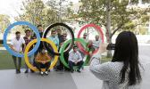 A group of students from Uruguay pose for a souvenir picture on the Olympic Rings set outside the Olympic Stadium in Tokyo