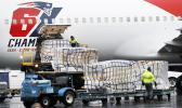Palettes of N95 respirator masks are off-loaded from the New England Patriots football team's plane