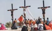Ruben Enaje, center, dressed as Jesus, is seen nailed on cross