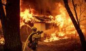 Flames consume a home in Magalia, California, Friday.