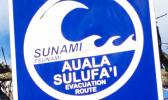 A sign directs people to the tsunami escape route on Samoa's Lalomanu Beach.