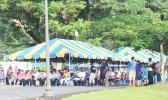 Crowds of people waiting under tents at TBAS to cash their stimulus checks
