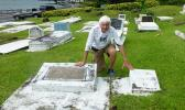 Tom Blake touches the two gravestones in Pago Pago, of his friend Mark Flannery's parents