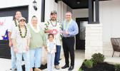 Retired U.S. Army Sergeant First Class Vaitogi Sani Taetuli and his family in front of their new home.