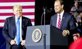 President Donald Trump, left, listens as Rep. Andy Barr, R-Ky., right, speaks at a rally