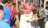 Rep. Su'a Alexander Eli Jennings (right) stirs pancake batter, while at the same time answering questions from members of the public during his demonstration last Friday at the Fagatogo Market Place where he make  gluten free breadfruit pancakes.  [photo: FS]