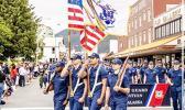 Leonrhee K. Alaimaleata carrying USCG flag in formation