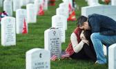 Victoria Ferguson is comforted by her husband, Phillip Ferguson, at the grave of her brother, David Taylor Miller, at Arlington National Cemetery on Nov. 11, 2015. Miller, who was killed in Afghanistan, would have marked his 25th birthday that Veterans Day. (Matt McClain/ The Washington Post)