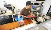 Saul De La Rosa prepares a tray of poke at Aloha Poke Shop in downtown Honolulu