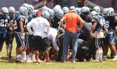 Samoana Sharks varsity squad huddling around one of their injured players