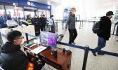 Staff members take passengers' body temperature at Tianhe International Airport in Wuhan