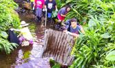 Youth volunteers remove scrap metal from the Vaitele stream